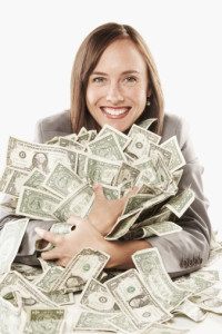 Businesswoman holding large pile of banknotes and smiling, portrait