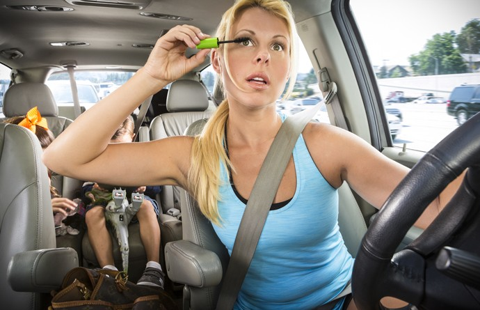 Soccer mom applies makeup while driving kids in minivan.